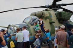 De volwassenen en de kinderen letten op helikopter mi-24 Stock Afbeelding