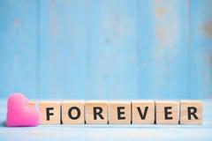 De VOOR ALTIJD houten kubussen met roze hart vormen decoratie op blauwe lijstachtergrond en exemplaarruimte voor tekst Liefde, Ro royalty-vrije stock foto