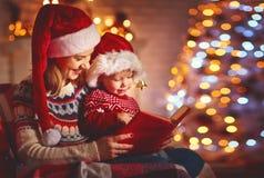 De vooravond van Kerstmis familiemoeder en baby die magisch boek thuis lezen stock foto