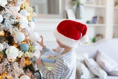 De vooravond van Kerstmis Jongen in santahoed die zich dichtbij Kerstmisboom bevinden met gift De decoratie van Kerstmis Nieuw ja royalty-vrije stock foto's
