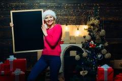 De vooravond van Kerstmis Kerstmisvrouw die een zwart bureau voor tekst houden De zwarte ruimte van het raadsexemplaar De voorber royalty-vrije stock foto's