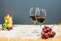 De vooravondtoejuichingen van het nieuwe jaar met twee glazen rode wijn en druiven Royalty-vrije Stock Afbeeldingen
