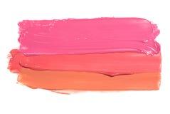 De voorbeelden van verschillend glanzen lipglossen die naar beneden op een witte achtergrond stromen stock foto