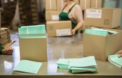 De voorbeeldenboeken van handpakken op productlijn Stock Afbeelding