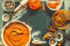 De voorbereiding van de pompoenpastei met ingrediënten en keukengereedschap op donkere rustieke achtergrond, hoogste mening, kade Royalty-vrije Stock Foto's