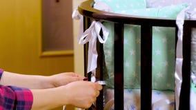 De voorbereiding voor een pasgeboren kind wordt voorbereid op de vergadering Het vouwen van het houten meubilair van kinderen, wi stock videobeelden