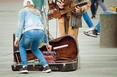 De voorbijgangers geven geld aan een straatmusicus royalty-vrije stock afbeelding