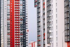 De voorgevel van een high-rise gebouw met rode witte en grijze strepen De bouw met meerdere verdiepingen tegen de blauwe hemel Ac royalty-vrije stock foto's