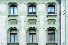De voorgevel van een oud steengebouw Vensters en decoratieve gipspleistercijfers royalty-vrije stock foto
