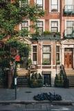 De voorgevel van een typisch huis van New York met buigt, vuilnis in zwarte bakken voor het royalty-vrije stock afbeeldingen