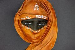 In de voorgrond een masker die een typisch gezicht van een vrouw met Afrikaanse eigenschappen en met burqa afschilderen royalty-vrije stock fotografie