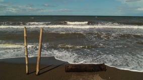De voorgrond van bamboepolen, Zeewater in het strand door milde wind wordt gedreven die stock video