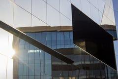 De voormuur van het glasvenster façade van een modern bureaugebouw met een bezinning van de een andere bureaubouw die zich in de stock foto's