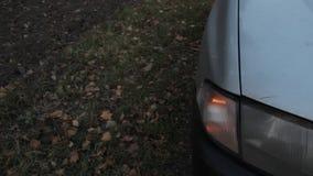 De voorrichtingaanwijzer van een auto op de kant van de weg die, en een deel van de auto knipperen stock videobeelden