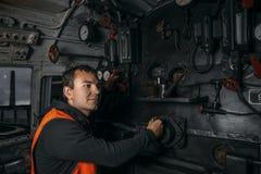 De voortbewegingsbestuurder in de werkplaats in de cabine van de locomotief controleert de hefbomen royalty-vrije stock foto's