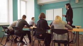 De vooruitgang van de controlestudenten van de vrouwenleraar tijdens een les in klaslokaal stock videobeelden