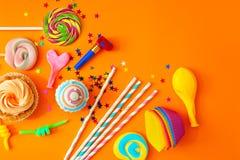 De voorwerpen van de verjaardagspartij op oranje achtergrond, stock afbeelding