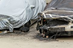 De voorwielen, de kappen en de bumpers van twee auto's leden tijdens een brand Beschadigde auto's die met een film op een stadsst royalty-vrije stock foto