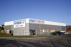 De voorzijde van de Screwfixwinkel met parkeerterrein en blauwe hemelachtergrond stock foto