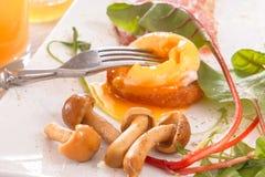De vork doordringt de dooier van gestroopte eieren Ontbijt met ei, bacon, paddestoelen en greens Royalty-vrije Stock Afbeelding