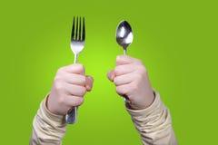 De vork en de lepel van de holding Stock Afbeelding