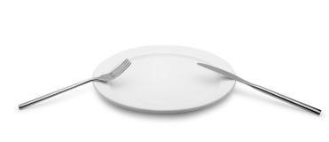 De vork en een mes liggen op een plaat Royalty-vrije Stock Fotografie