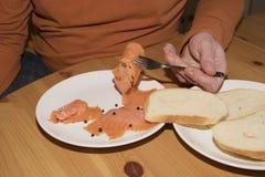 De vork van de bejaardeholding en het eten van gerookte zalm met plak van wit brood Eenzaamheid en enig concept royalty-vrije stock afbeelding