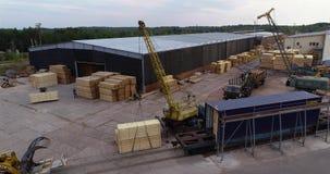 De vorkheftruck draagt een houten straal, Vervoer van lading in de fabriek Het werkproces in een houtbewerkingsfabriek stock video