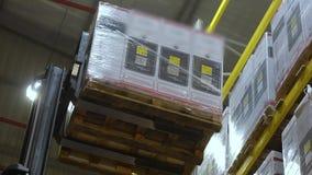 De vorkheftruck in een groot modern pakhuis, een vorkheftruck verwijdert de doos uit de hoogste plank stock videobeelden