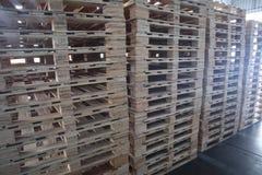 De vorkheftruck en de houten pallets hopen in het ladingspakhuis op voor vervoer en logistiek royalty-vrije stock foto's
