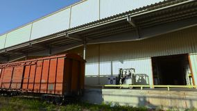 De vorkheftruck levert de lading aan de treinauto De goederentrein van de ladingswagen stock videobeelden