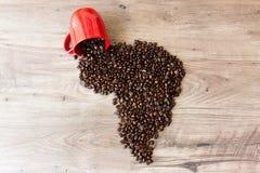 De vorm van Afrika van koffiebonen wordt opgemaakt bovenop een houten lijst die van uit van een kop uitgieten die Stock Fotografie