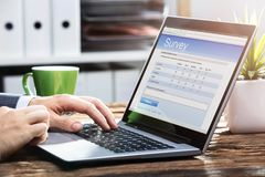 De Vorm van Businesspersonfilling online survey op Laptop stock afbeelding
