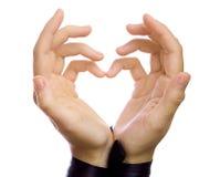 De vorm van hart die door vrouwelijke handen gestalte wordt gegeven. Stock Foto's
