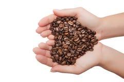 De vorm van het hart die van koffiebonen wordt gemaakt in handen Royalty-vrije Stock Afbeeldingen