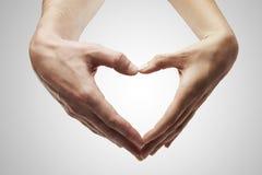 De vorm van het hart die van vrouwelijke en mannelijke handen wordt gemaakt Stock Fotografie