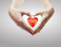 De vorm van het hart die van vrouwelijke en mannelijke handen wordt gemaakt Royalty-vrije Stock Foto