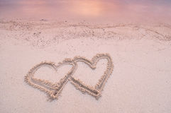 De vorm van het liefdehart met de hand geschreven op het zand Royalty-vrije Stock Fotografie