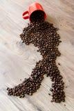 De vorm van Italië van koffiebonen wordt opgemaakt bovenop een houten lijst die van uit van een kop uitgieten die Royalty-vrije Stock Afbeelding
