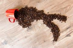 De vorm van Italië van koffiebonen wordt opgemaakt bovenop een houten lijst die van uit van een kop uitgieten die Stock Afbeeldingen