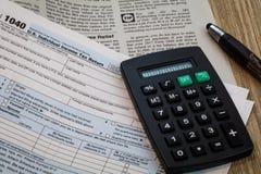 De vormen van de belastingsvoorbereiding met generische pen en calculator, geen gespecificeerd jaar Stock Fotografie