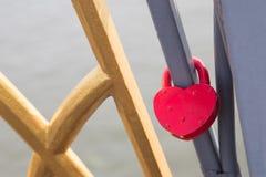 De vormslot van het liefdehart met metaalketting op brug Stock Foto