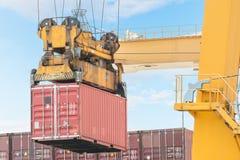 De vrachtschip van de containerlading met werkende brug i van de kraanlading Stock Foto's