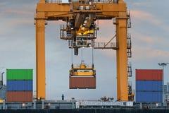 De vrachtschip van de containerlading met werkende brug i van de kraanlading Royalty-vrije Stock Afbeeldingen