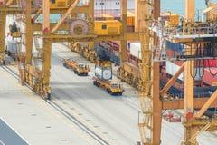De vrachtschip van de containerlading met werkende brug i van de kraanlading Stock Afbeeldingen