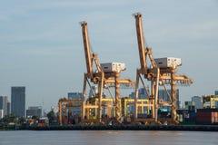 De vrachtschip van de containerlading met werkende kraanbrug in scheepswerf bij schemer voor Logistische Invoer-uitvoer royalty-vrije stock afbeelding