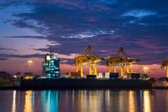 De vrachtschip van de containerlading met werkende kraanbrug in scheepswerf bij zonsopgang Royalty-vrije Stock Afbeeldingen