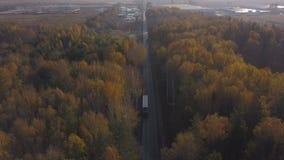 De vrachtvrachtwagen die van de hommelmening zich op autoweg bewegen op achtergrond de herfstbos stock video