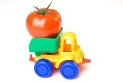 De vrachtwagen die van het stuk speelgoed een tomaat draagt Stock Foto's