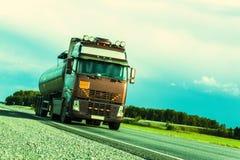 De vrachtwagen draagt een chroomtank met olie op de weg Foto van de rand Royalty-vrije Stock Afbeeldingen